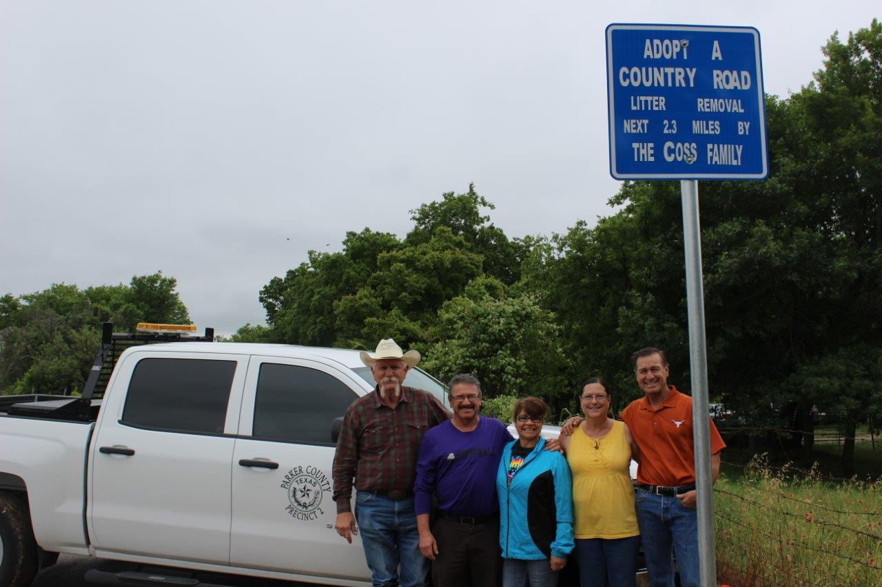 Picture of Commissioner Peacock with the Coss Family for adopting a county road
